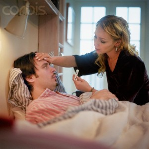 Woman Taking Care of Ill Man Lying in Bed